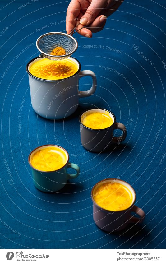 Turmeric latte in cup and spice powder. Warm detox turmeric milk Herbs and spices Beverage Hot drink Milk Cup Health care Healthy Natural Blue Yellow Colour