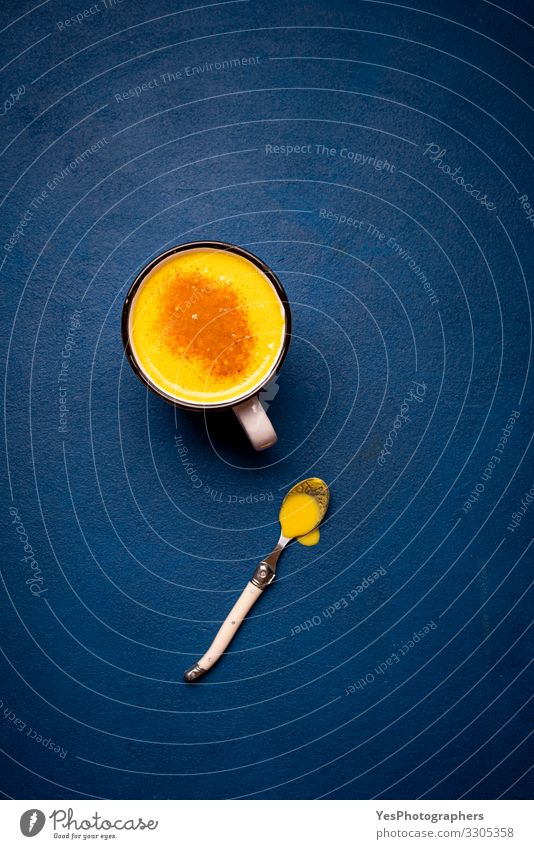 Turmeric latte on a blue table. Healthy drink. Yellow milk cup Herbs and spices Beverage Hot drink Natural Curcuma Longa above view antioxidant Aromatic