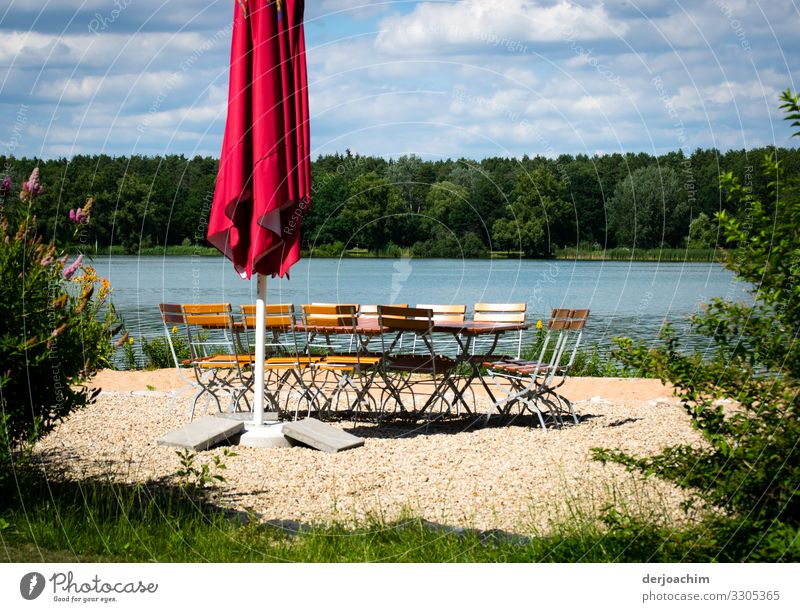 Pure idyll. A lake , in front of a parasol with a group of chairs in a circle. In front green and in the background forest. Joy Relaxation Summer Environment