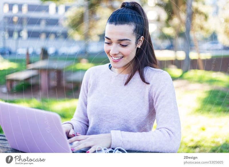 Young beautiful woman sitting outdoors while working with computer Lifestyle Happy Beautiful Academic studies Work and employment Business Computer Notebook