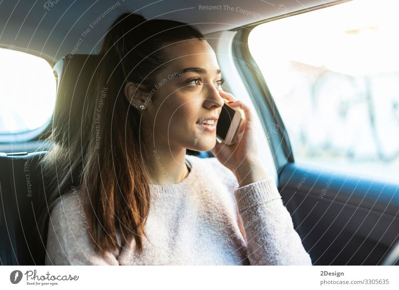 Young beautiful woman with ponytail talking on the phone in the back seat of car female mobile phone business pretty urban tied-up girl people cute drive