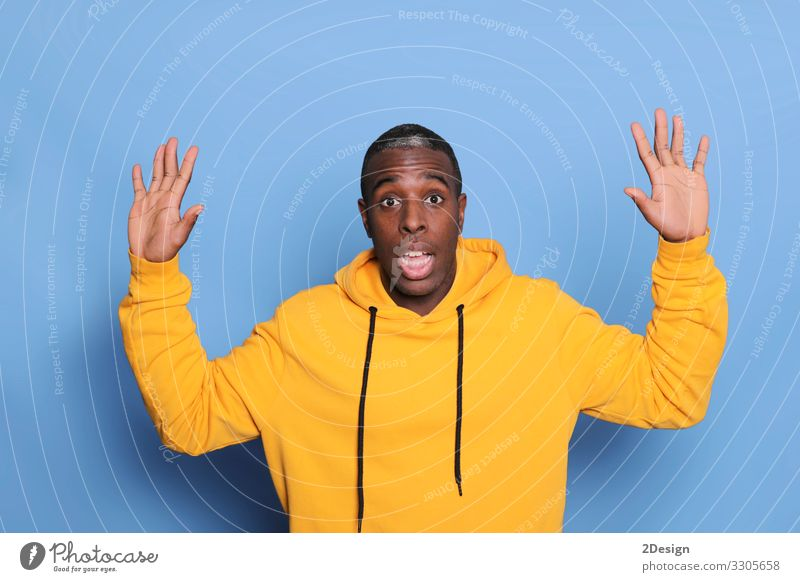 attractive man looking suprised isolated on blue background Human being Youth (Young adults) Man Blue Green Young man Black 18 - 30 years Face Adults Funny