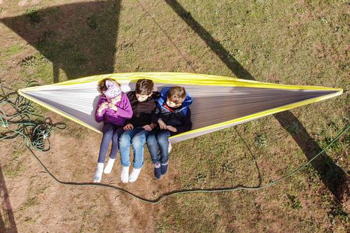 Three kids relaxing on a hammock. Air view Joy Happy Beautiful Relaxation Calm Leisure and hobbies Playing Summer Summer vacation Garden Child Human being