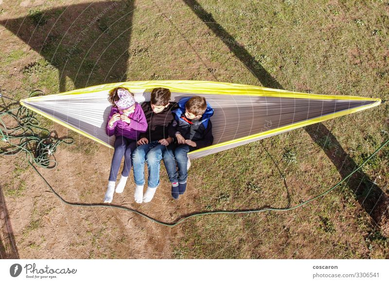 Three little kids sitting on a hammock Joy Happy Beautiful Relaxation Calm Leisure and hobbies Playing Summer Summer vacation Garden Child Human being Toddler