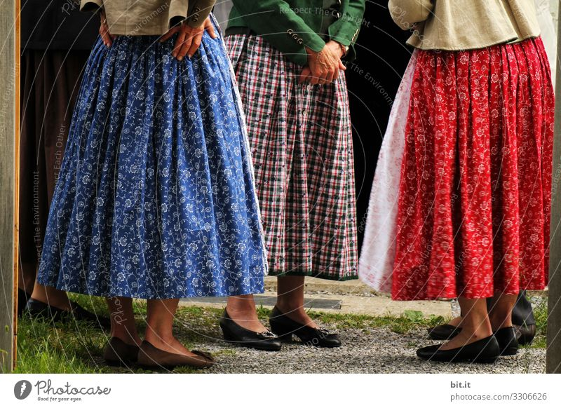 Three women in dirndls with skirts, aprons, patterns, checks and flowers stand together in Bavaria for a round of talks. A group of ladies in traditional costume stand together for village gossip, conversation, ratcheting, exchange, morning pint gathered in a circle.