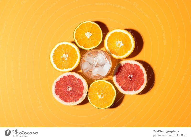 Citrus fruits and glass with ice in sunlight. Fruit Orange Breakfast Organic produce Vegetarian diet Diet Cold drink Healthy Eating Fresh Bright Red above view