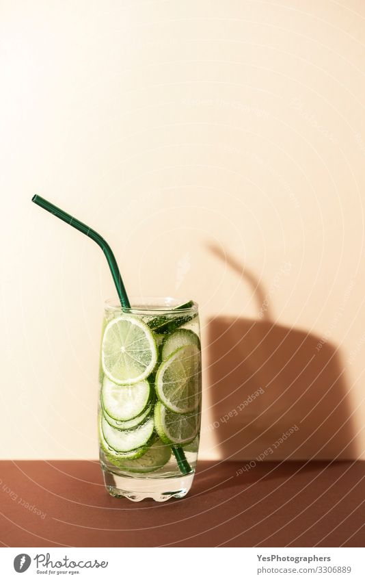 Cucumber and lime water.Cold green lemonade. Fruit Beverage Cold drink Lemonade Glass Straw Red antioxidant drink brown shades Copy Space cucumber and lime