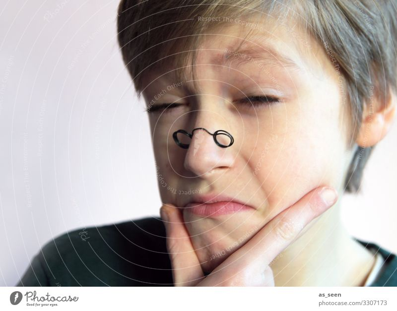 Boy looks through small glasses with sceptical eyes Looking monocle Eyeglasses Looking into the camera Portrait photograph Human being Masculine Face