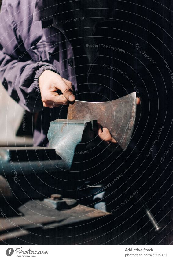 Crop craftsman checking axe in workshop blade grinder sharpen using tool male metalwork industry handmade machine electric guy electrical busy job heavy worker