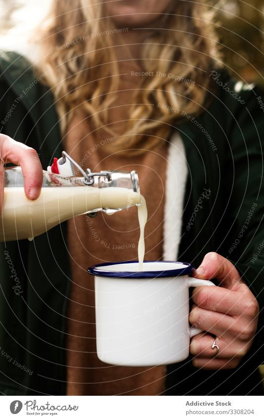 Anonymous woman filling mug of milk during picnic pour dairy bottle casual female rural countryside autumn drink cup beverage prepare tasty ingredient cream