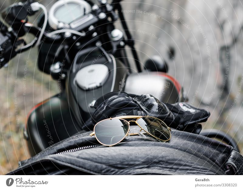 sunglasses and gloves on the motorcycle fuel tank Style Transport Motorcycle Fashion Clothing Leather Accessory Sunglasses Gloves Glass Metal Brown