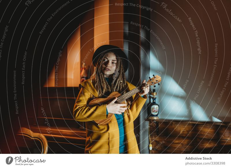 Stylish young woman playing guitar hipster music stylish serious millennial ukulele hawaiian female stand focused concentrated practicing musician instrument