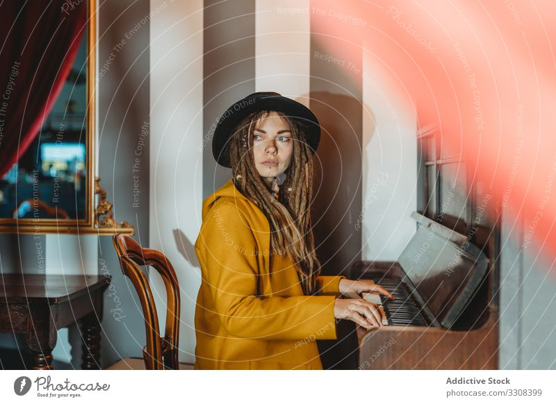 Hipster millennial woman playing piano dreadlocks hipster music stylish serious sit female focused concentrated practicing musician instrument art pianist