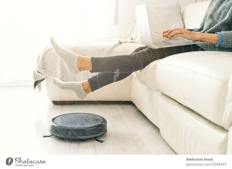 Woman sitting on sofa with feet on robotic vacuum cleaner woman smart home technology floor wireless appliance machine household domestic modern contemporary