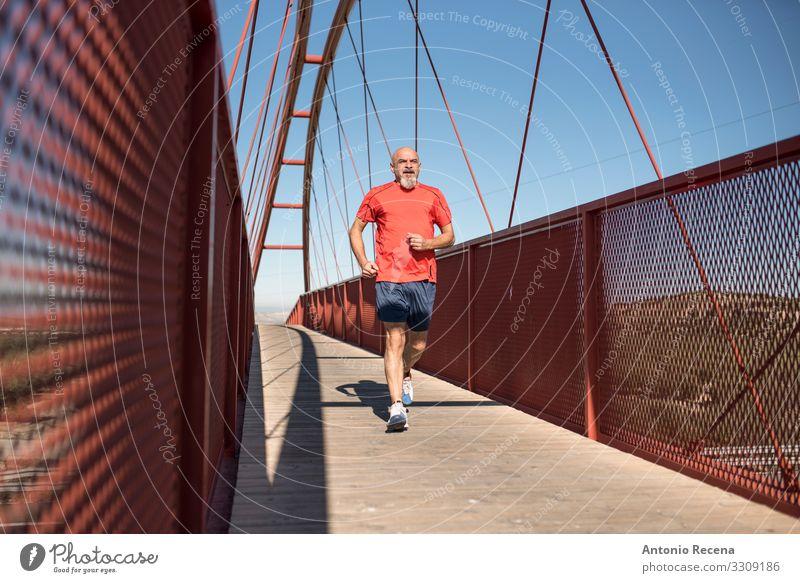 Senior runner training on a bridge Lifestyle Sports Human being Man Adults Bridge Bald or shaved head Beard Old Fitness Red White Serene Effort Runner senior