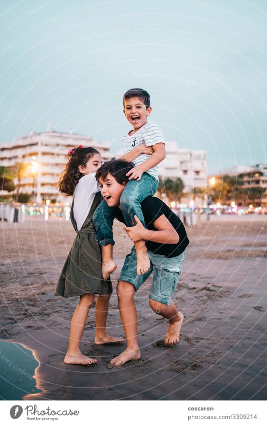 Children havig fun on the beach at sunset Lifestyle Joy Happy Beautiful Leisure and hobbies Playing Vacation & Travel Summer Summer vacation Beach Ocean