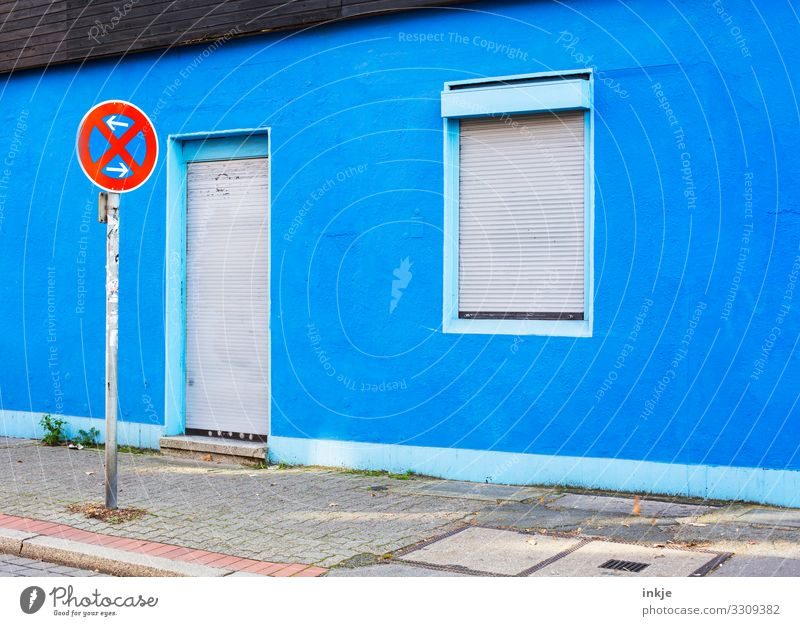 Do not stop and do not visit Deserted Sidewalk Facade Window Door Sign Road sign No standing Blue Closed Venetian blinds Colour photo Multicoloured