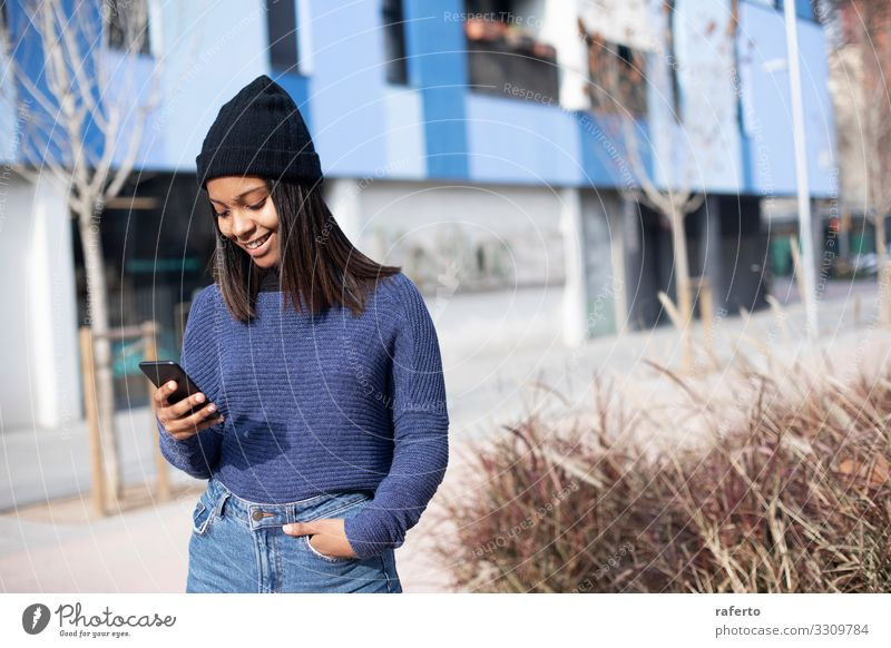 young beautiful woman standing while using a mobile phone Lifestyle Happy Beautiful Telephone PDA Technology Internet Human being Feminine Young woman