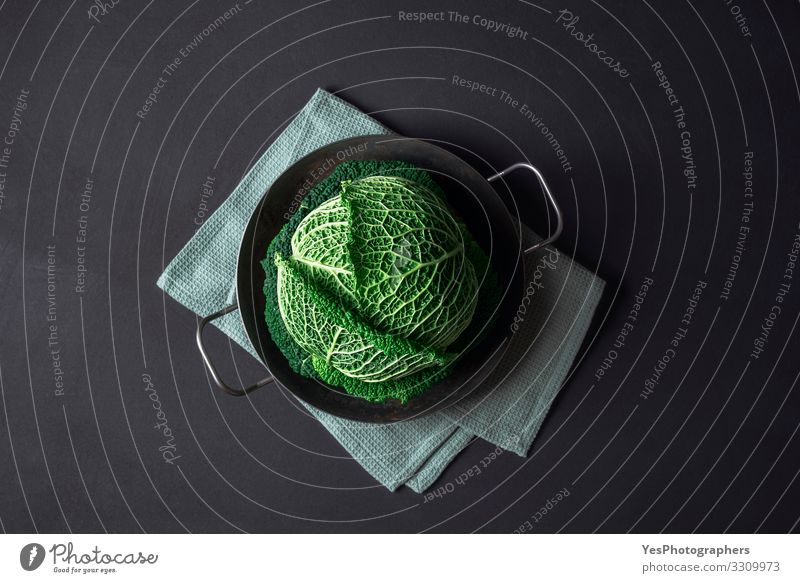 Savoy cabbage in an iron pan on black table. Cooking cabbage Healthy Eating Plant Green Food Natural Fresh Kitchen Vegetable Organic produce Vegetarian diet