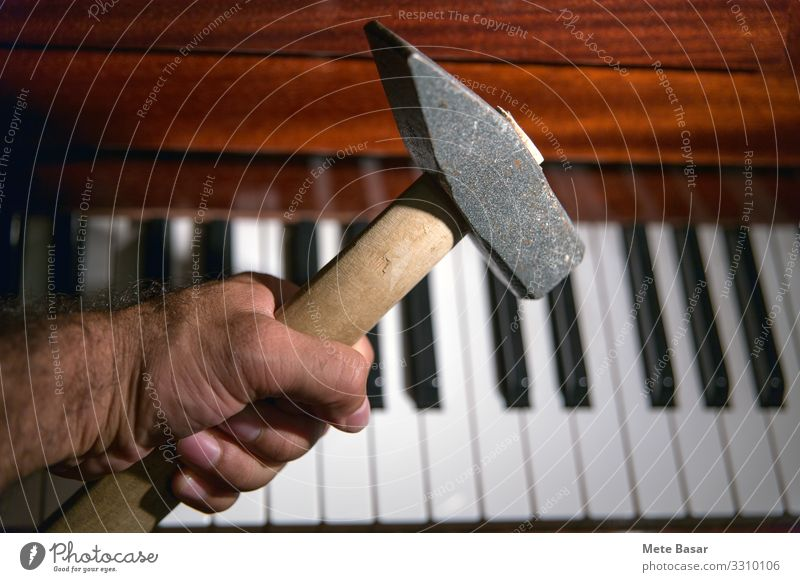 Intention to destroy a piano with a heavy hammer. Style Music Man Adults Hand Piano Wood Threat Brown Black White Hatred Destruction key Classical Approach bad
