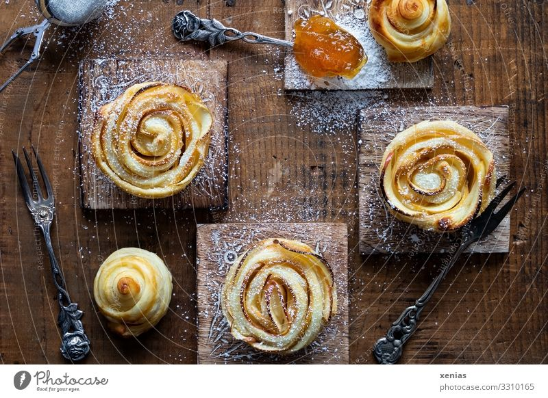 Three apple roses with icing sugar and apricot jam on wooden board Food Apple Dough Baked goods Cake Jam Confectioner`s sugar Apricot jam Nutrition Breakfast