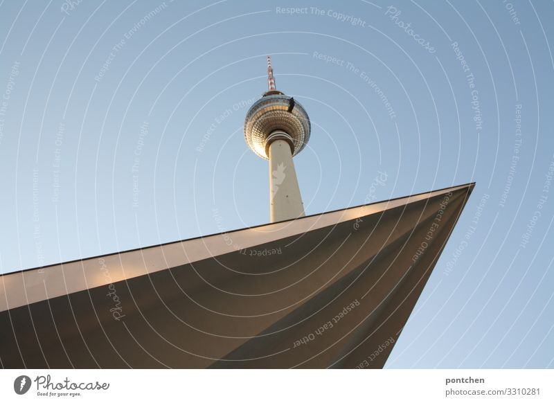 TV tower berlin in front of a blue sky. Tip of a roof juts into the picture. architecture. Landmark. Television tower Tourist Attraction Tall Point Colour photo