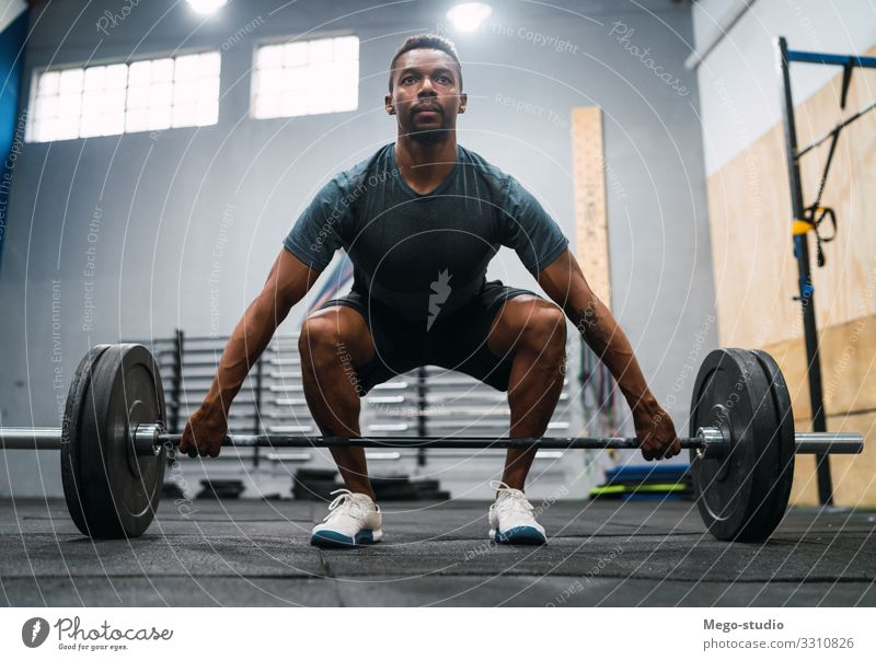 Crossfit athlete doing exercise with a barbell. Lifestyle Body Sports Man Adults Fitness Athletic Muscular Strong Black Power Concentrate Barbell workout