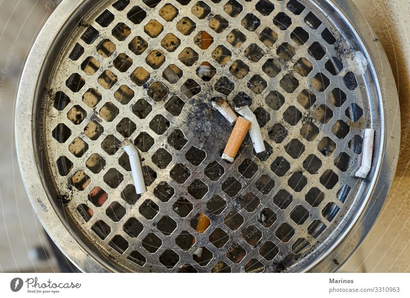 Closeup view of big ashtray with dropped cigarettes. Illness Stand Dirty Ashtray Cigarette butt health smoke Unhealthy addiction Cancer garbage tobacco