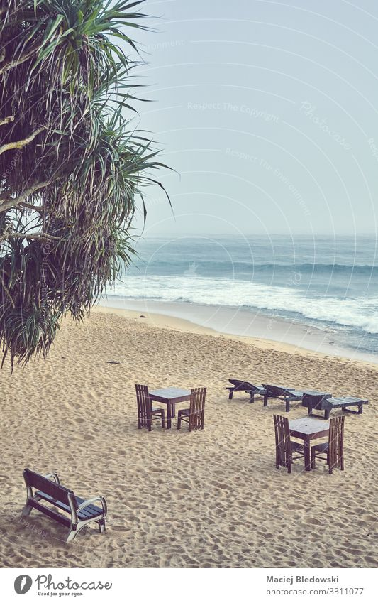 Empty beach on a rainy day. Exotic Vacation & Travel Tourism Summer vacation Beach Ocean Island Chair Table Nature Sky Bad weather Rain Plant Sadness Dark Wet