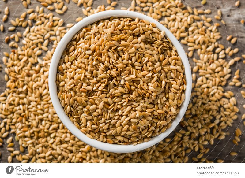 Golden flax seeds in white bowl on wooden table. Healthy Eating White Food photograph Dish Wood Yellow Exceptional Agriculture Dry Good Grain Vegetarian diet