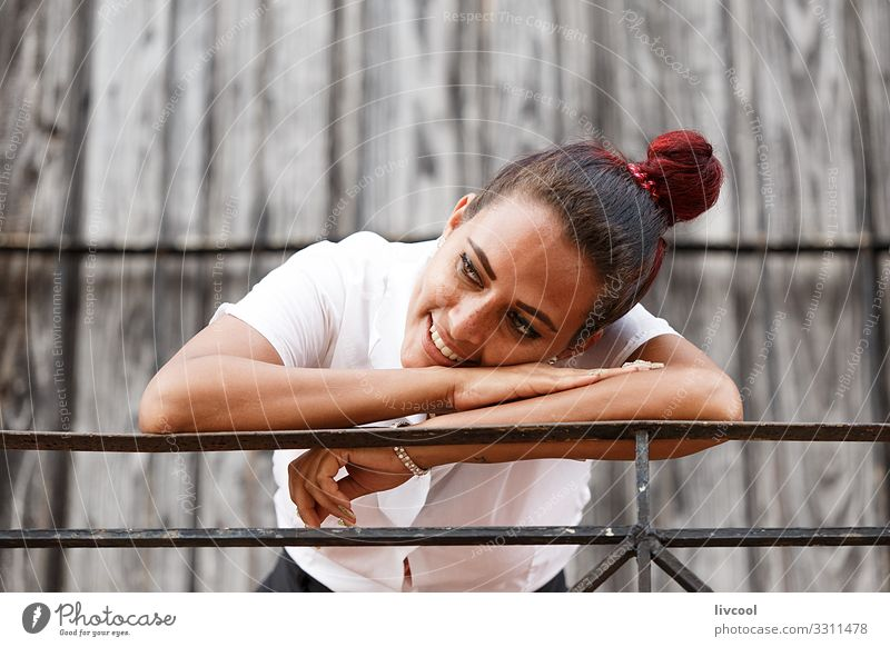 Beautiful young cuban woman leaning on a railing Lifestyle Happy Island Human being Young woman Youth (Young adults) Woman Adults Facade Balcony Street To enjoy