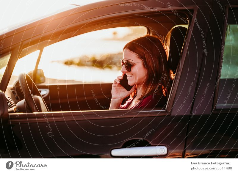 young woman driving a car at sunset and using mobile phone. travel concept Youth (Young adults) Woman Car Driving Sunset Beach Driver Vacation & Travel