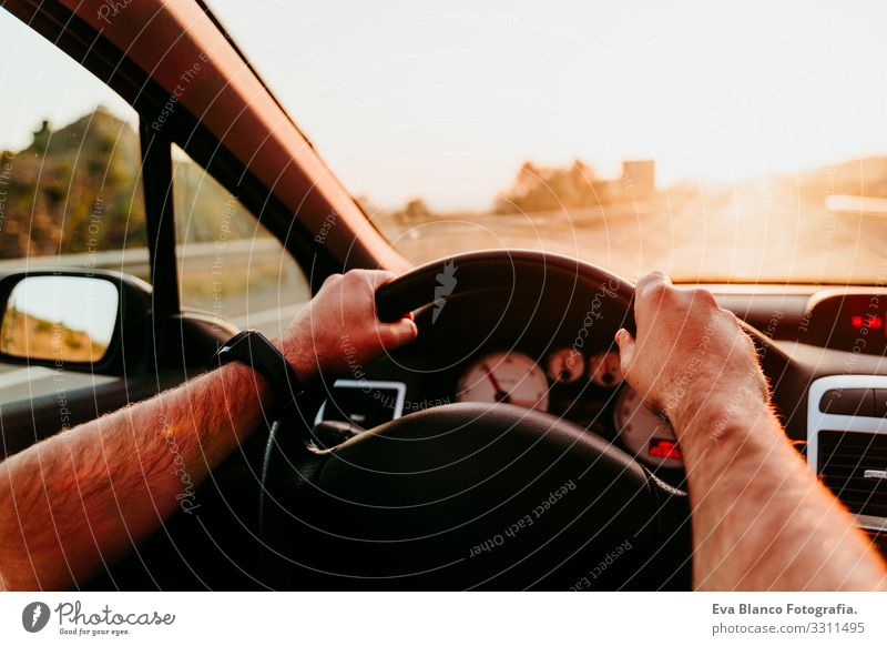 unrecognizable man holding wheel and driving at sunset. travel concept Man Driving Car Sunset Street Vacation & Travel Trip Caucasian Unrecognizable pov