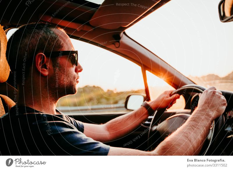 young man holding wheel and driving at sunset. travel concept Man Driving Car Sunset Street Vacation & Travel Trip Caucasian Youth (Young adults) Driver