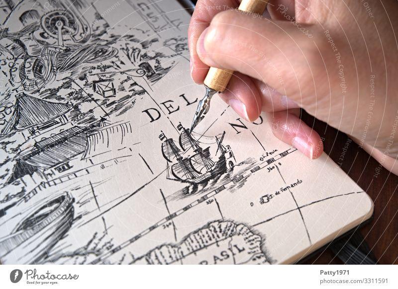 Detailaufnahme einer Hand, die mit einer Zeichenfeder ein Segelschiff im Stile antiker Landkarten eine Zeichnung in einem Skizzenbuch anfertig