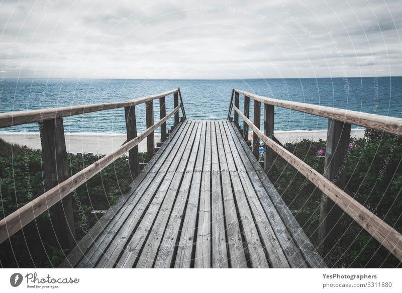 Wooden footpath towards sea on Sylt island on a rainy day Summer Ocean Sand North Sea Bridge Gloomy Moody Perspective Frisian island German beach Germany