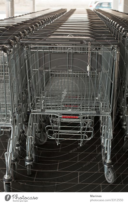 Shopping carts in a supermarket. Food Business Line Supermarket Retail sector Storage row background buy empty trolley consumer aisle Consumption Hypermarket