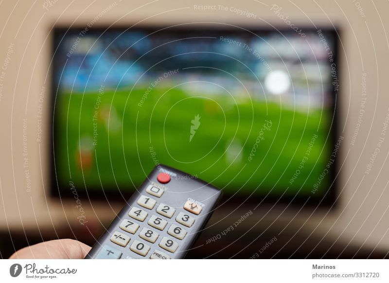 TV remote control and an open television as background. Entertainment Sports Computer Screen Technology Internet Man Adults Hand Media Television Observe Smart
