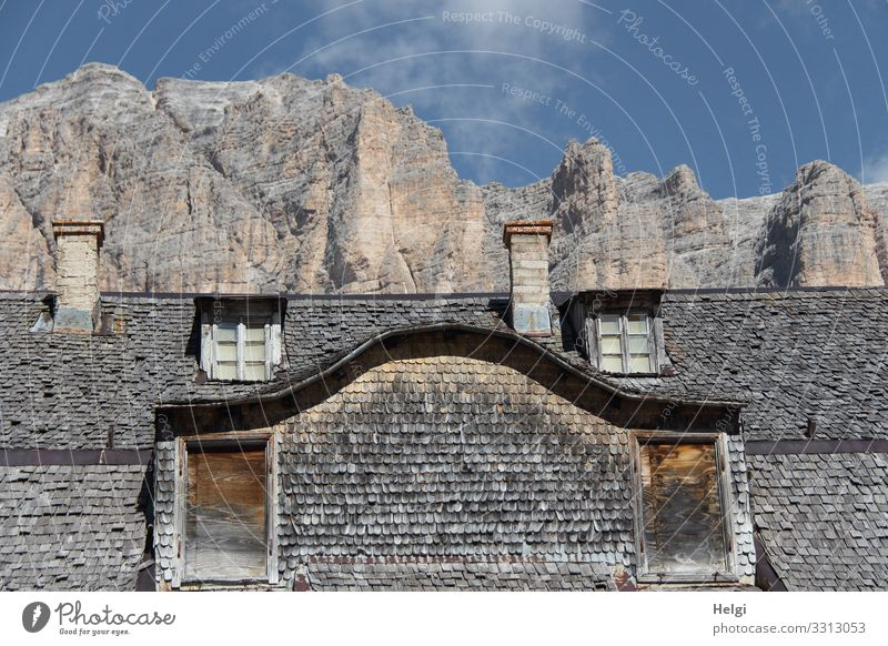 old house clad with wooden shingles stands in front of a gigantic mountain in the Dolomites Environment Nature Sky Clouds Autumn Beautiful weather Rock Alps
