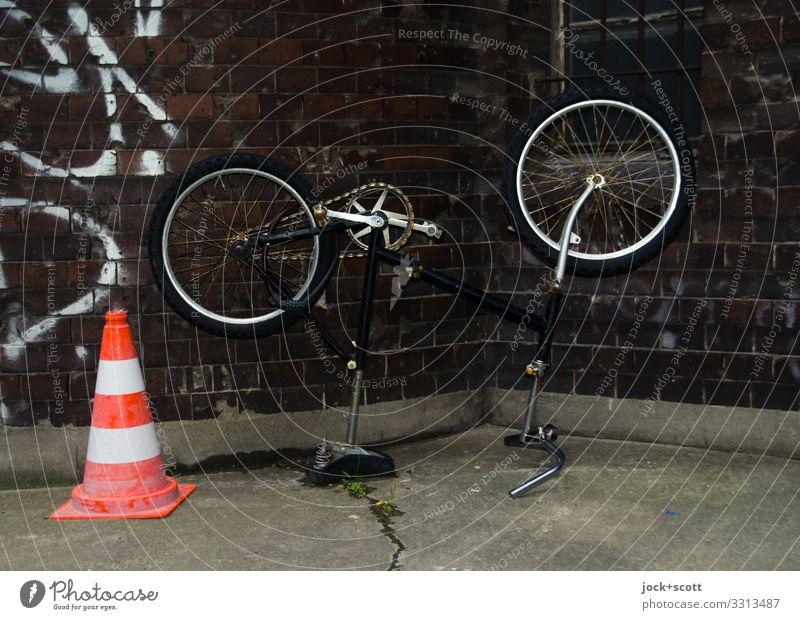 who turned the wheel? Design Prenzlauer Berg Wall (building) Backyard Traffic cone Graffiti Dark Gloomy Moody Safety Idea Problem solving Mountain bike