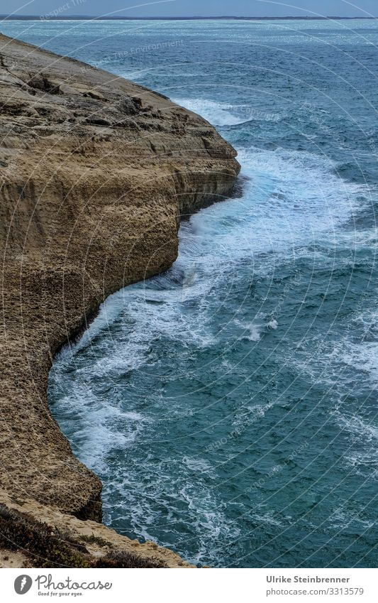 Rugged cliff in the Mediterranean Sea Ocean Mediterranean sea Waves Water Surf Cliff Rock Sardinia Coast Steep Stone somber Evening curt Nature Landscape