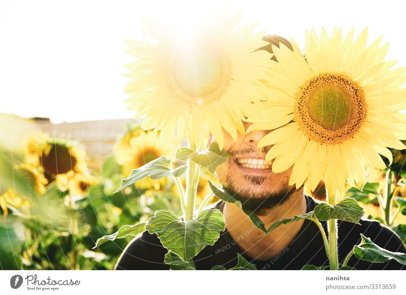 Young man enjoying the day in a field of sunflowers Face Life Sun Human being Masculine Man Adults Nature Spring Weather Beautiful weather Flower Beard To enjoy