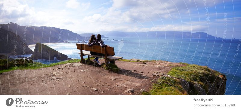 Panoramic view of a couple in the best bench of the world panoramic landscape Loiba Galicia natural summer water nature beautiful island fishing grow green
