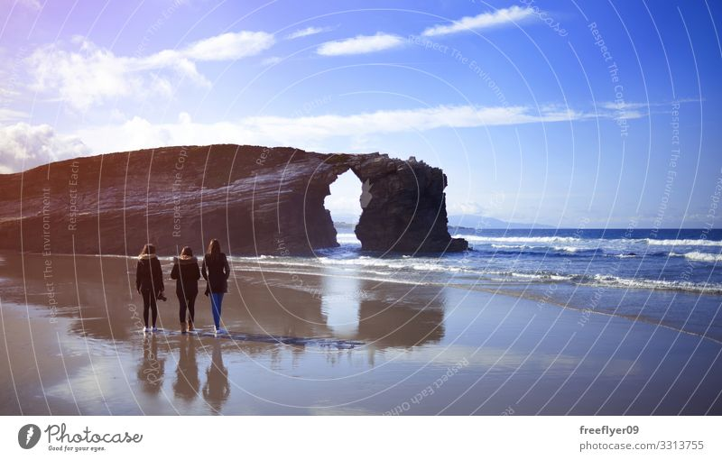 Three young women walking on Cathedrals Beach in Galicia three beach cathedrals ribadeo galicia tourism spain hiking ocean coast natural atlantic scenic tide