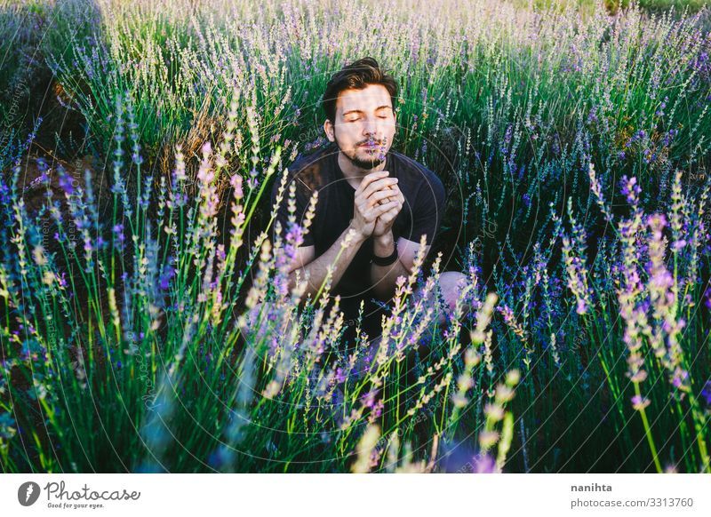 Young man in a field of flowers masculinity new gender handsome spring shadow light sun sunny lavender male young beard bearded casual wear natural real