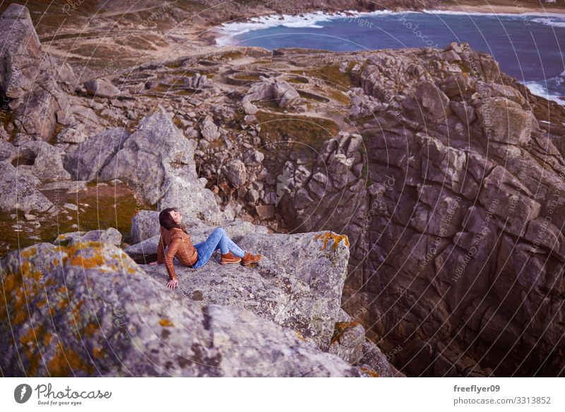 Woman sitting on a cliff near Baroña Castro in Galicia Barona celtic galicia spain hiking tourism nature coastline rocks landscape young woman one person beach