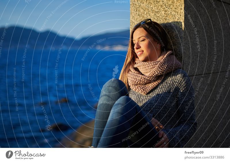 Young woman enjoying the sunlight near the ocean in Vigo young sea water rocks vigo galicia winter autumn blue travel enjoyment hiking coast coastal sky