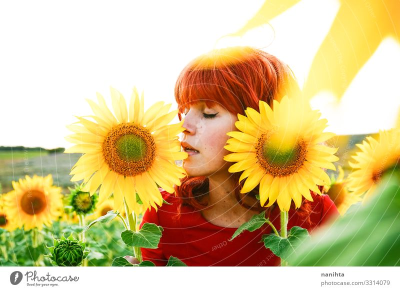 Lovely redhead woman enjoying the day in a field o sunflowers Woman Human being Nature Youth (Young adults) Young woman Summer Beautiful Red Flower Calm Joy