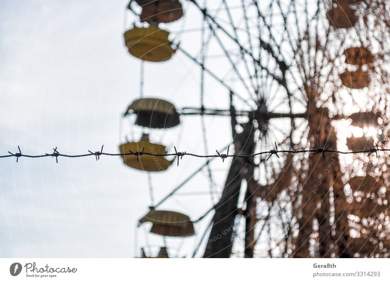 barbed wire and carousel in amusement park in Chernobyl Vacation & Travel Tourism Trip Plant Sky Autumn Tree Park Metal Old Threat Blue Yellow Dangerous