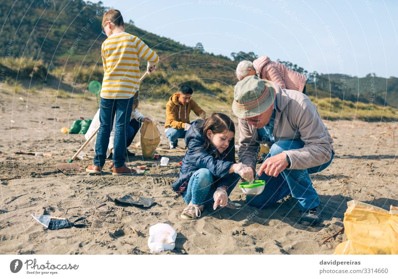 Volunteers cleaning the beach Beach Child Work and employment Human being Woman Adults Man Grandfather Family & Relations Group Environment Sand Sieve Plastic
